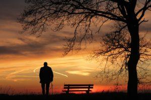 Zdjęcie starszego mężczyzny na tle zachodzącego słońca